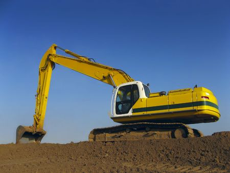 An Excavator against a blue sky Stock Photo