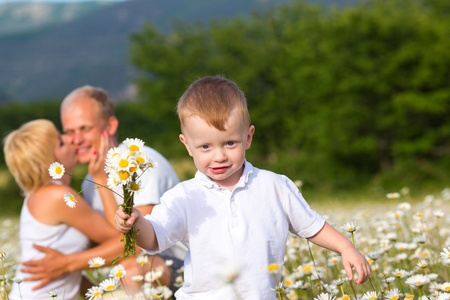 Family playing on the camomile meadow photo