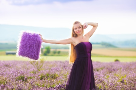 Blond girl with purple pillow on lavender field photo