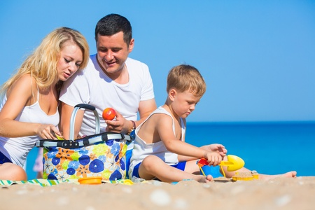 Family of three person on the beach photo