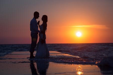 Bruidspaar op het strand bij zonsondergang Stockfoto