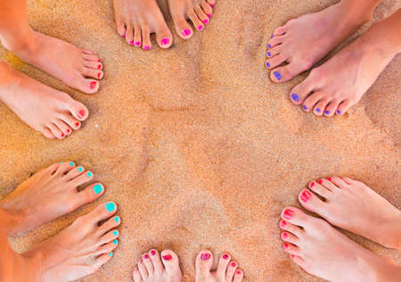 beach feet: Six pairs of woman feet on the sand
