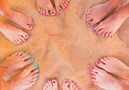 Zes paren van de vrouw voeten op het zand