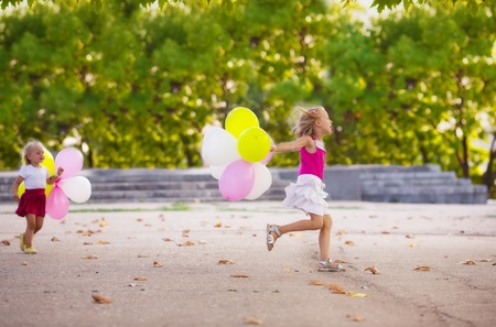 Two little girls with balloons in the park photo