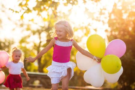 Twee kleine meisjes met ballonnen in het park