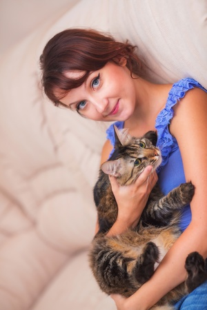 Beautiful young woman at home with cat photo