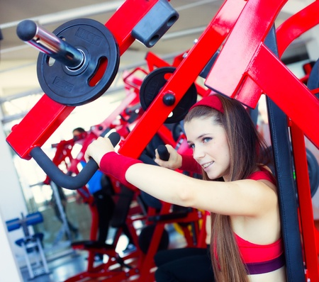 Young beautiful woman training in gym photo