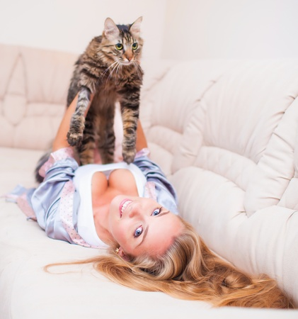 Beautiful young woman at home playing with cat photo
