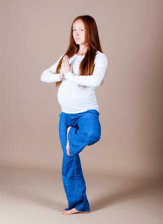 Pregnant woman making yoga figure photo