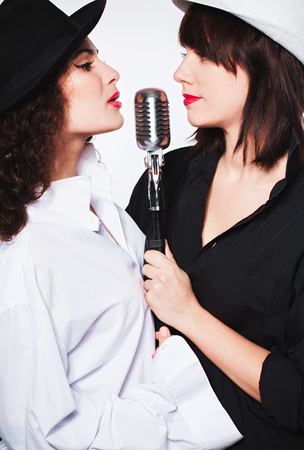 Two young girl singing to the microphone photo
