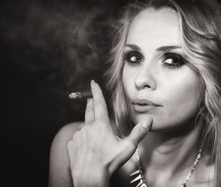 Beautiful blond woman portrait with cigar photo