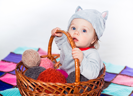 Little baby sitting in basket with balls of wool photo