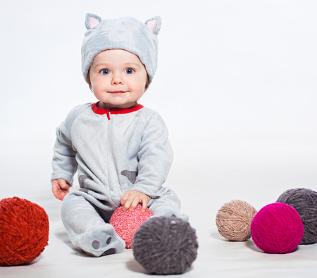 Little boy in cat costume playing with balls of wool photo