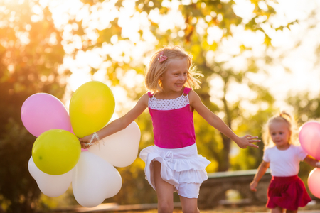 Two sisters playing in the park with balloons photo