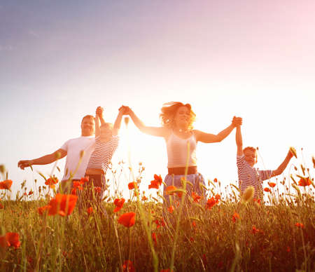 Happy family playing on the poppy meadow photo
