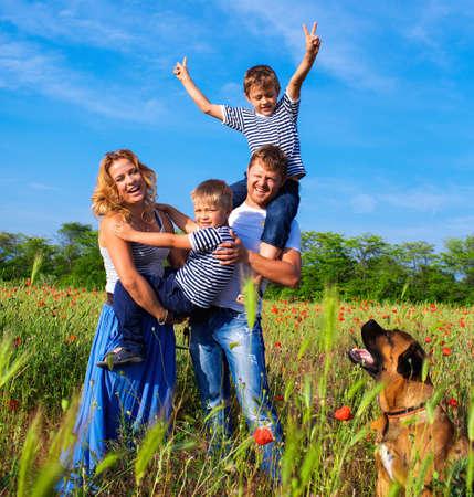 ポピーの草原で遊んで幸せな家族
