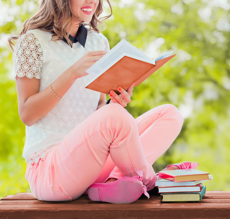 Young beautiful girl reading book in the garden photo