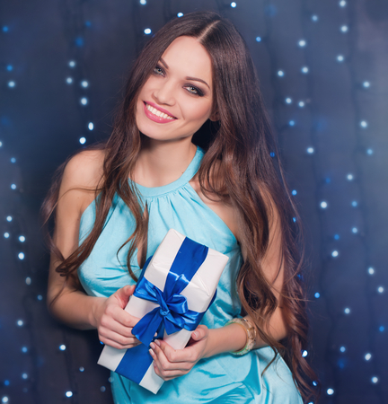 Beautiful girl with long hair holding present in hands Stock Photo
