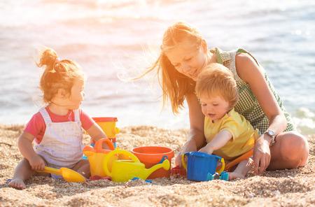 ni�os jugando: Madre que juega con los ni�os en la playa