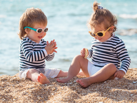 cute man: Little boy and girl playing on the beach Stock Photo