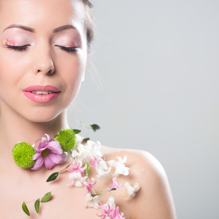 nacked: Beautiful woman with flowers on the showlder. Space for text.