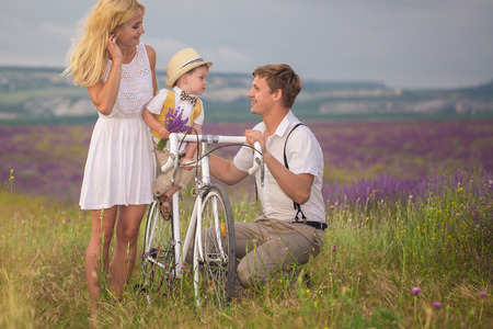 three person: Happy young family of three person walking on lavender field
