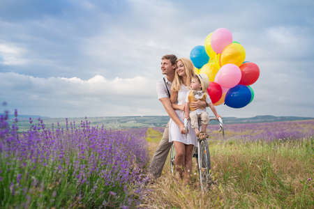 色の風船とラベンダー畑の上を歩く 3 人の幸せな若い家族 写真素材