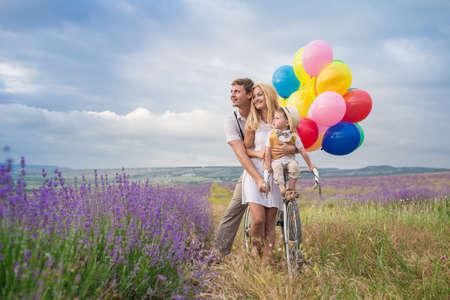 Gelukkig jong gezin van drie persoon lopen op lavendel veld met kleur ballonnen