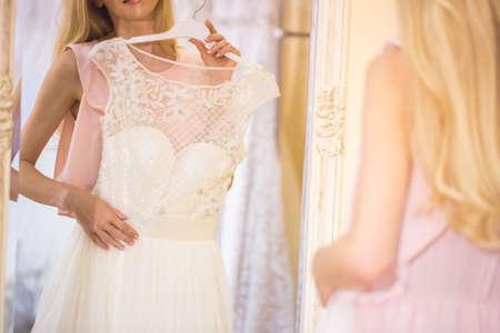 美しい若い女性のイブニング ドレスを選択します。 写真素材