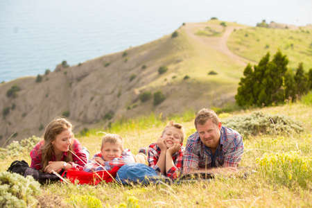 four people: Family of four people looking to beautiful seascape in mountains