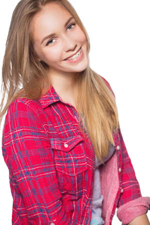overbite: Close up portrait of smiling teen girl showing dental braces. Isolated on white background. Stock Photo