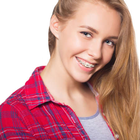 Close up portrait of smiling teen girl showing dental braces. Isolated on white background. Stock Photo
