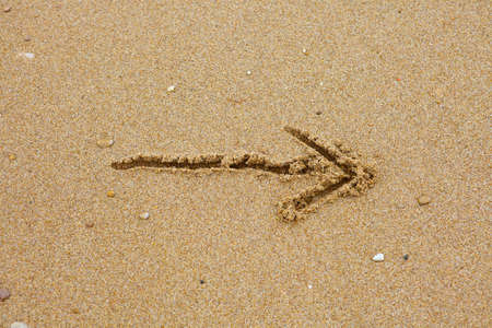 sand drawing: Drawn arrow on the sand