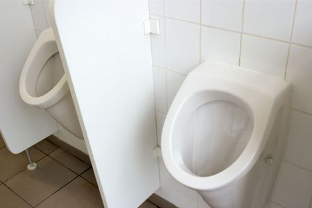 Mens toilet inside, two urinals, white wall photo