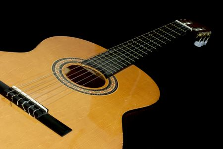 Neck and head of an acoustic guitar, isolated black background with copy-space photo