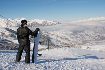 Snowboarder standing at the top of the slope photo