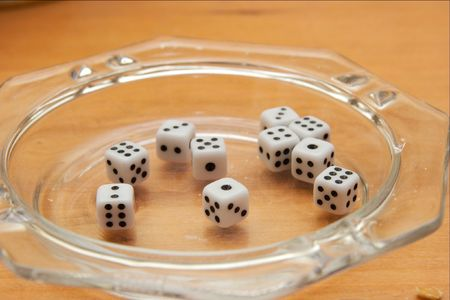 Ten small white dices in an ashtray photo