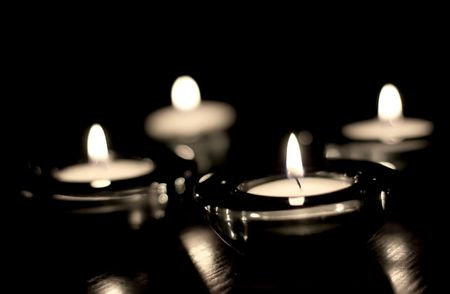four candles blazing in the night, soft focus Banco de Imagens