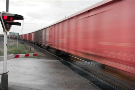 Railway crossing with motion blurred ast freight train photo