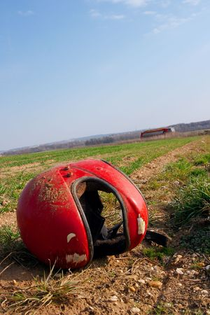 agricultural area: Abandoned red helmet in an agricultural area
