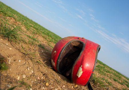 casco rojo: roto casco rojo tirado en un campo