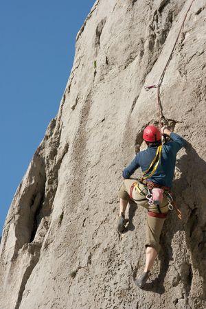 Alpiniste sur une paroi rocheuse haute  Banque d'images