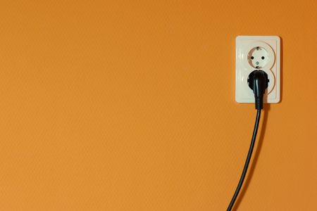 White electric outlet on an orange wall photo