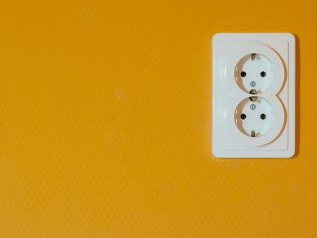 grounded plug: electric outlet socket on orange wall