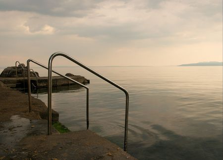 Rocks sea shore, overcast sky, stairs into the water photo