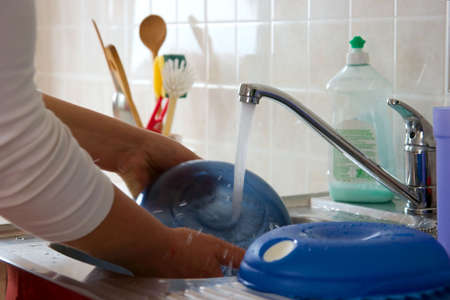 Woman washing dishes in flowing water photo