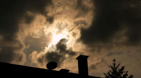 Dark stormy sky with the silhouette of a roof with chimney photo