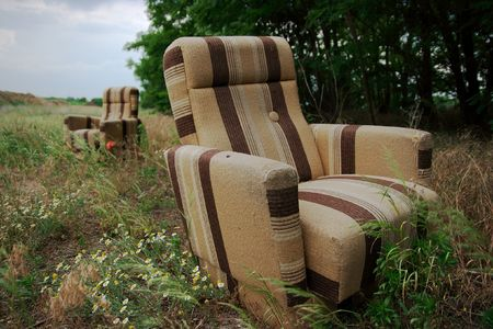 discarded: Two discarded armchairs on a field Stock Photo