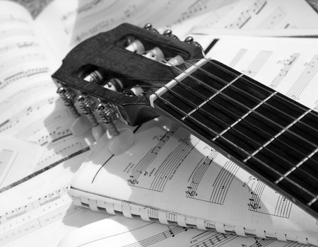 sheetmusic: Acoustic guitar with sheet music in the background Stock Photo