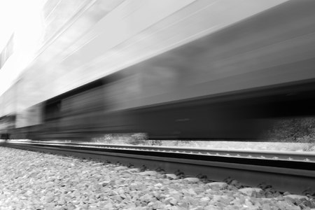 Train moving fast with motion blur. Black and white high-key image photo